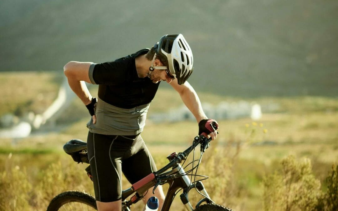 Man on a mountain bike experiencing lower back pain